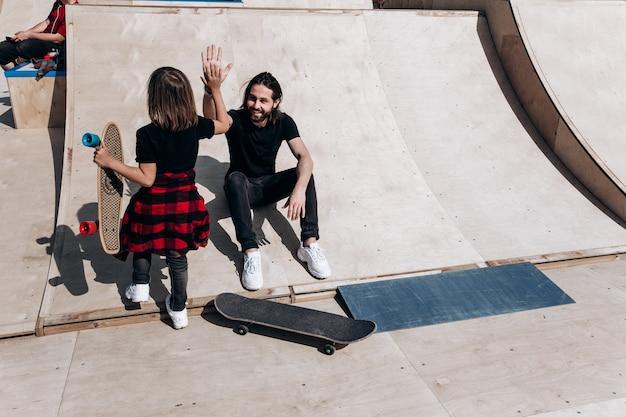 De jonge vader en zijn zoon gekleed in de stijlvolle vrijetijdskleding zitten en hebben samen plezier op de glijbaan naast de skateboards in een skatepark op de zonnige warme dag.