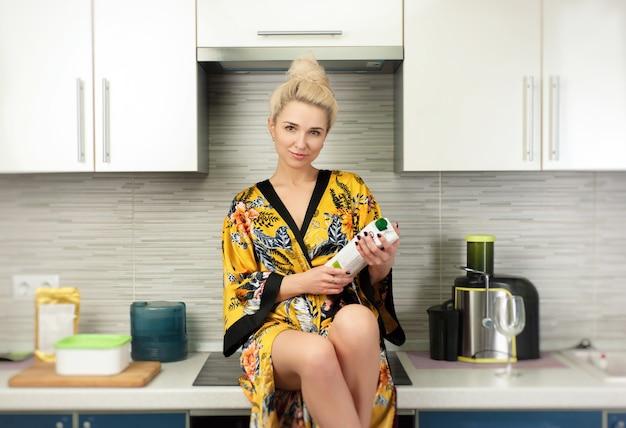 De jonge vegan vrouw in de keuken met een pakje gezond natuurlijk sap