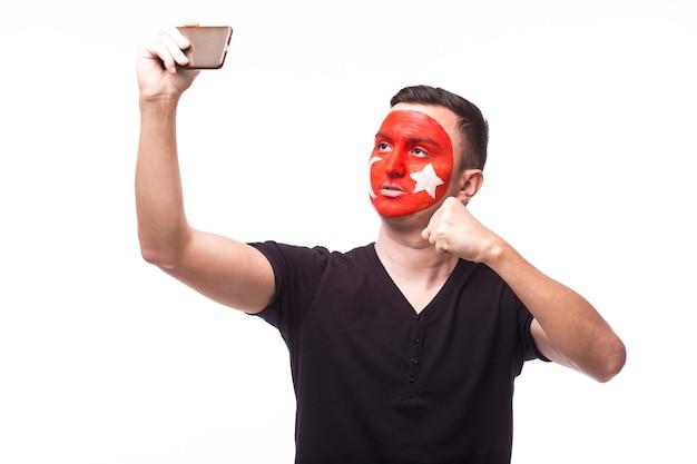 De jonge ventilator van de de mensenvoetbal van tunesië maakt selfie op witte muur wordt geïsoleerd die