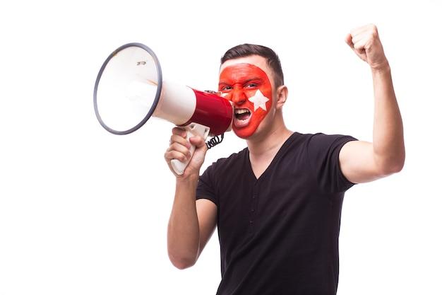 De jonge ventilator van de de mensenvoetbal van tunesië met megafoon die op witte muur wordt geïsoleerd