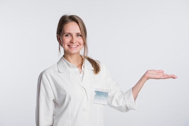 De jonge verpleegster die van de artsenvrouw en exemplaarruimte voor product of tekst voorstellen tonen. kaukasische vrouwelijke medische professional geïsoleerd op wit