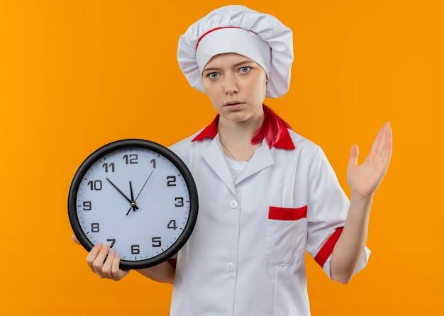 De jonge verraste blonde vrouwelijke chef-kok in eenvormige chef-kok houdt klok vast en houdt hand omhoog geïsoleerd op oranje muur