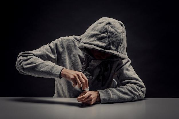 De jonge verslaafde bereidt cocaïne voor. drugsgebruik en misbruik van illegale stoffen.