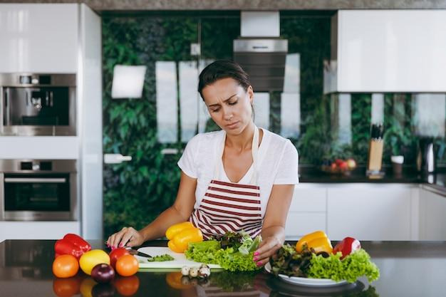 De jonge verwarde en bedachtzame vrouw in schort beslist wat ze in de keuken gaat koken
