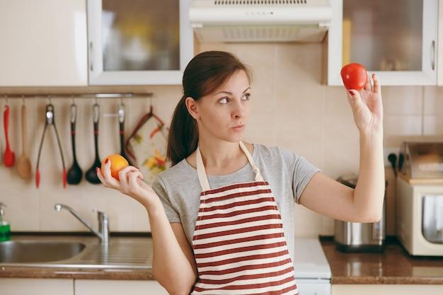 De jonge verwarde en peinzende vrouw in een schort besluit een rode of gele tomaat in de keuken te kiezen. dieet concept. gezonde levensstijl. thuis koken. eten koken.