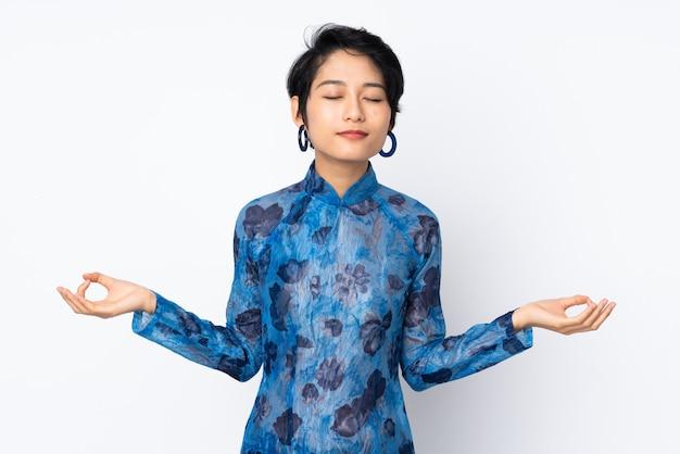 De jonge vietnamese vrouw met kort haar die een traditionele kleding over geïsoleerd wit in zen dragen stelt