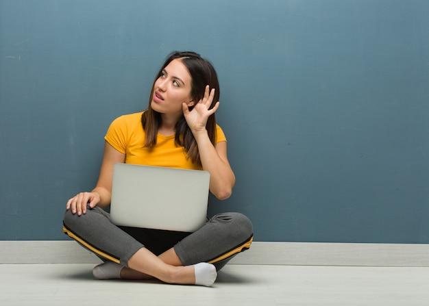 De jonge vloer van de vrouwenzitting met laptop probeert luisterend een roddel