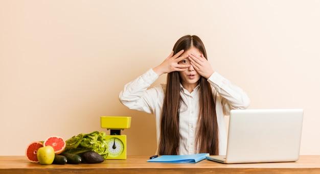 De jonge voedingsdeskundige chinese vrouw die met haar laptop werkt knipoogt door bang en zenuwachtige vingers.