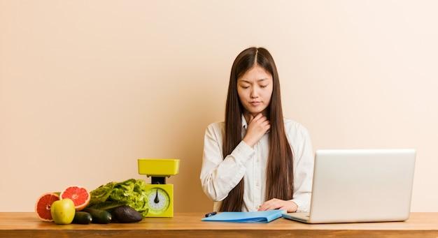 De jonge voedingsdeskundige chinese vrouw die met haar laptop werkt lijdt pijn in keel toe te schrijven aan een virus of een besmetting.
