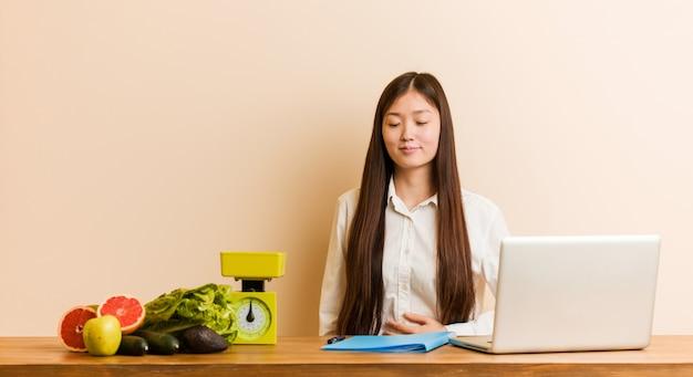 De jonge voedingsdeskundige chinese vrouw die met haar laptop werkt raakt buik