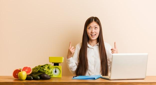 De jonge voedingsdeskundige chinese vrouw die met haar laptop werkt wijst op met beide voorvingers die omhoog een lege ruimte tonen.