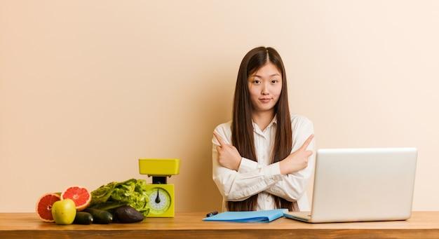 De jonge voedingsdeskundige chinese vrouw die met haar laptop werkt zijdelings richt, probeert tussen twee opties te kiezen.