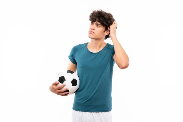 De jonge voetbalstermens over geïsoleerde witte muur die twijfels hebben en verwart gezichtsuitdrukking