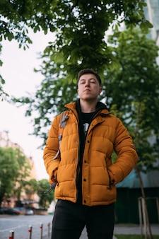 De jonge volwassen mens in een geel jasje en jeans loopt op een stadsstraat op een zonnige dag
