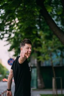 De jonge volwassen mens in een zwart t-shirt en jeans loopt op een stadsstraat