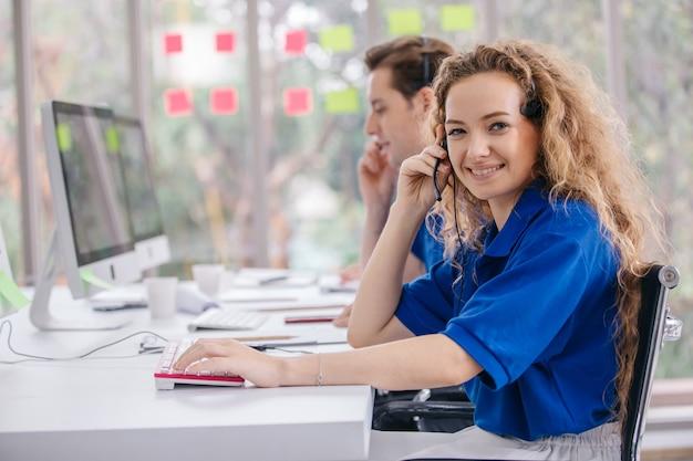 De jonge vriendelijke agent van de exploitantvrouw met hoofdtelefoons die in een call centre werken.
