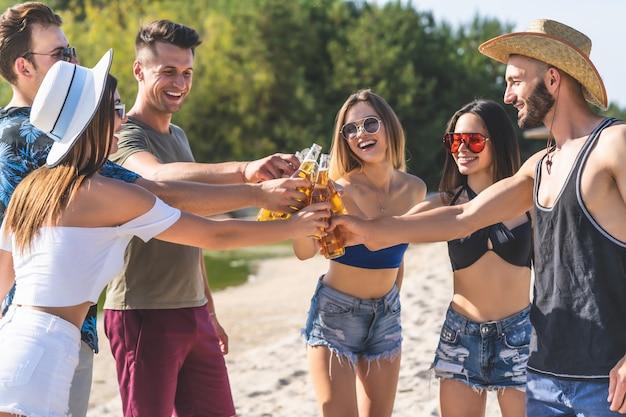 De jonge vrienden die flessen bier vasthouden op het strandfeest
