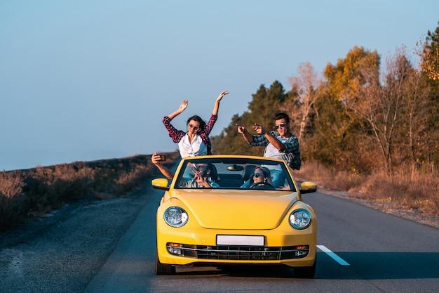 De jonge vrienden reizen in een gele cabrio
