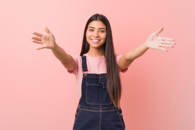 De jonge vrij arabische vrouw die jeansbroeken draagt draagt zeker het geven van een omhelzing aan de camera.
