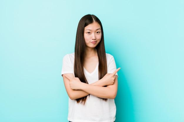 De jonge vrij chinese vrouw wijst zijdelings