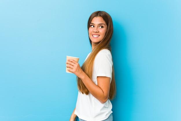 De jonge vrij kaukasische vrouw die een meeneemkoffie houden kijkt opzij glimlachend, vrolijk en aangenaam.