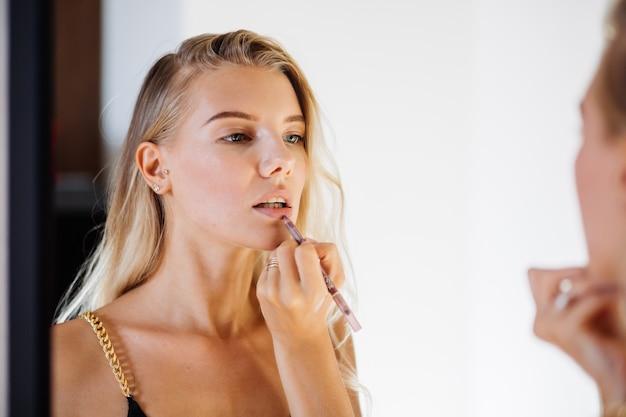 De jonge vrij leuke vrouw met natuurlijke make-up kijkt in spiegel en glimlach. zachte gladde schone huid.