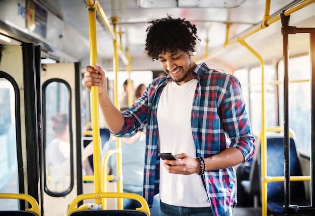 De jonge vrolijke knappe mens geniet van de muziek tijdens zijn rit en houdt aan de bar terwijl status in een bus.