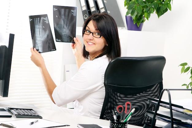 De jonge vrouw arts bekijkt röntgenstraal