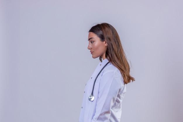 De jonge vrouw arts die in witte laag met phonendoscope aan zijprofiel kijken stelt status over wit geïsoleerde achtergrond