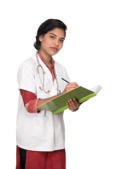 De jonge vrouw arts met stethoscoop schrijft in boek