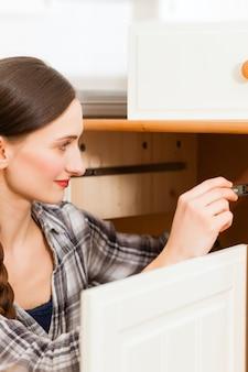 De jonge vrouw assembleert een kast