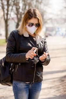 De jonge vrouw behandelt handen met een antiseptisch middel Premium Foto