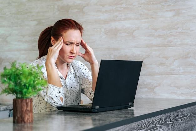 De jonge vrouw beklemtoonde en vermoeide met hoofdpijnzitting op kantoor