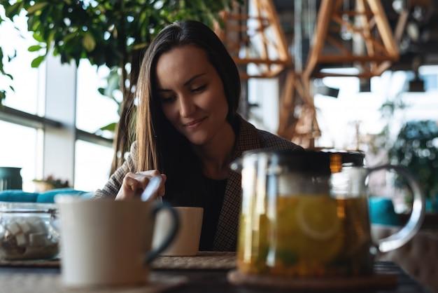 De jonge vrouw belemmert kruidenthee met duindoorn in de kop