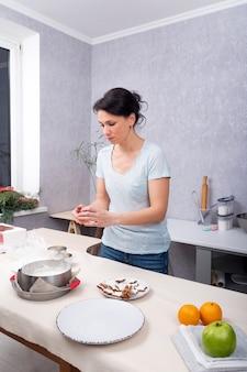 De jonge vrouw bereidt koekjes in de keuken voor. huisvrouw maakt de maaltijd klaar.