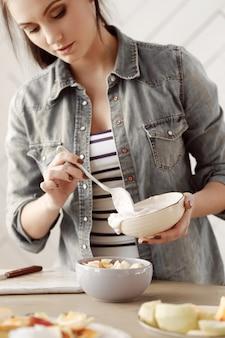De jonge vrouw bereidt ontbijt in de keuken voor