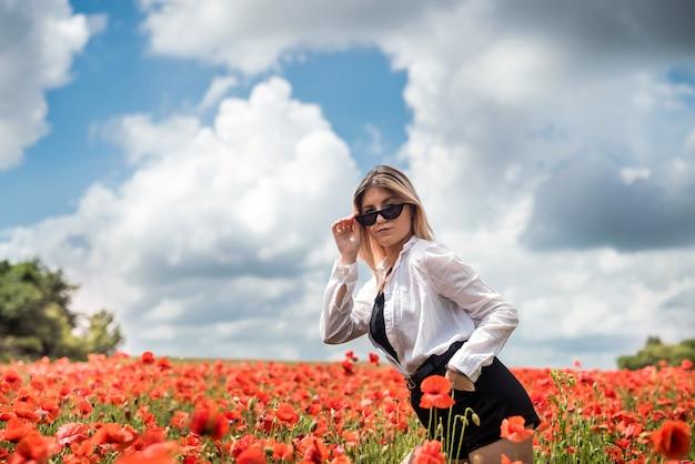 De jonge vrouw bevindt zich dichtbij bloeiend papavergebied. gelukkig meisje bij buiten, levensstijl