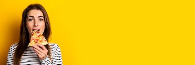 De jonge vrouw bijt een plak van hete verse pizza op geel