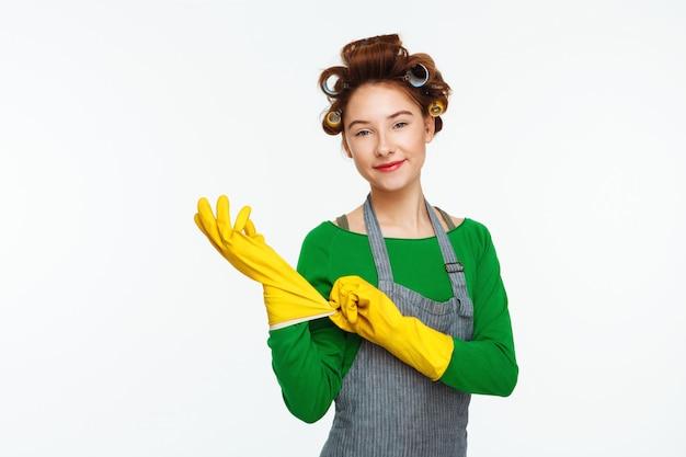 De jonge vrouw brengt rubberhandschoenen met krulspelden op haar aan
