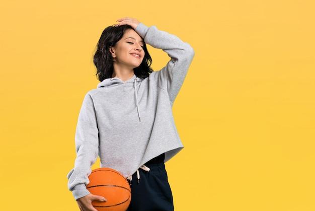 De jonge vrouw die basketbal speelt heeft iets gerealiseerd en de oplossing voor ogen