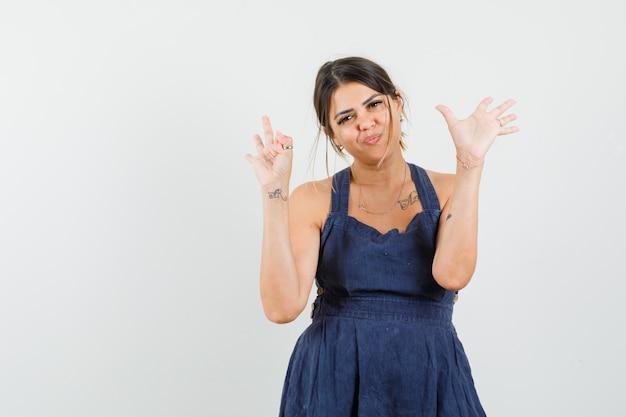 De jonge vrouw die drie en vijf vingers van toont dient kleding in en vrolijk kijkt