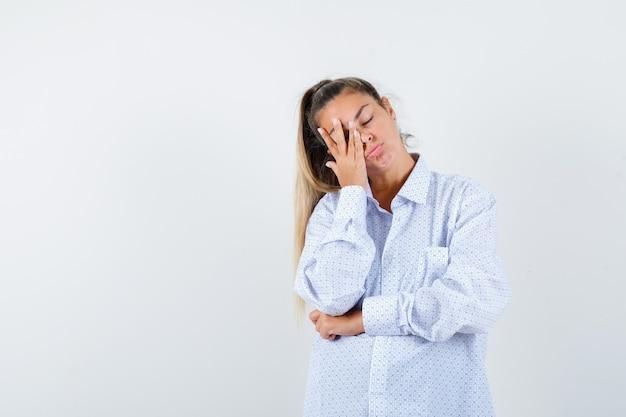 De jonge vrouw die een deel van het gezicht behandelt dient wit overhemd in en kijkt moe