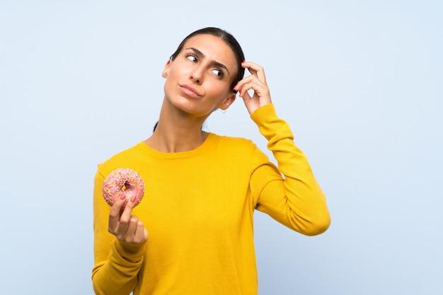 De jonge vrouw die een doughnut over geïsoleerde blauwe muur houden die twijfels hebben en met verwart gezichtsuitdrukking