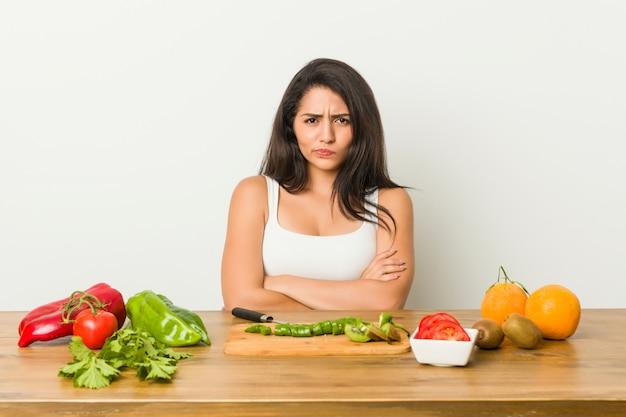 De jonge vrouw die een gezond maaltijd fronsende gezicht in ongenoegen voorbereiden, houdt wapens gevouwen.