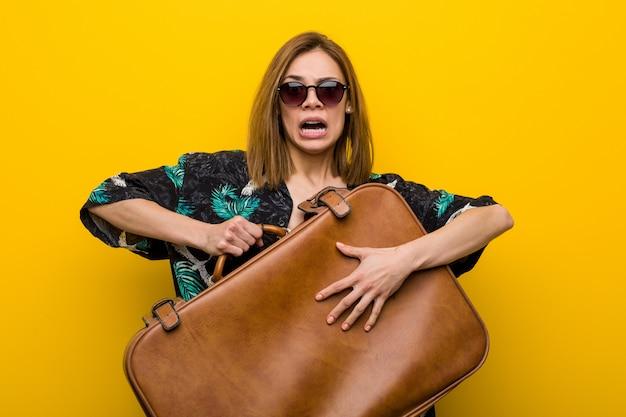 De jonge vrouw die een leerzak houdt doet schrikken over haar vakanties, heeft zij fobie om te vliegen.