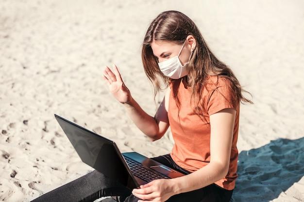 De jonge vrouw die een medisch masker draagt, zit op het strand met laptop