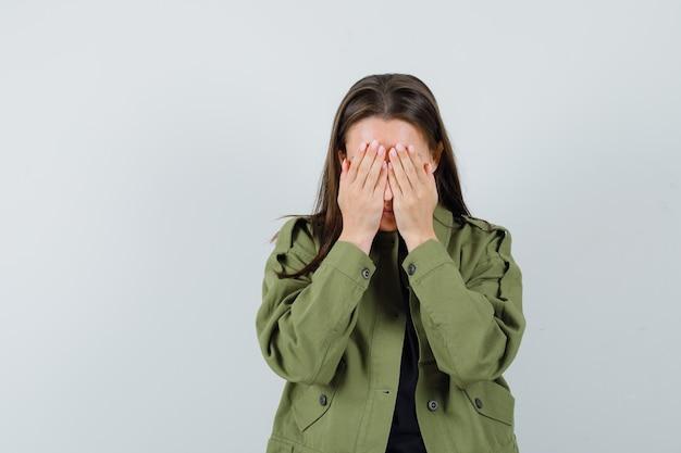 De jonge vrouw die gezicht behandelt met dient groen jasje in en kijkt van streek, vooraanzicht.
