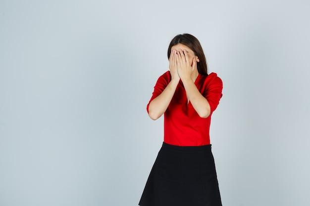 De jonge vrouw die gezicht behandelt met dient rode blouse, zwarte rok in en kijkt beschaamd