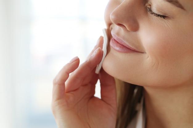 De jonge vrouw die gezichtsmake-up met samenstellingsvlekkenmiddel verwijdert, veegt af.