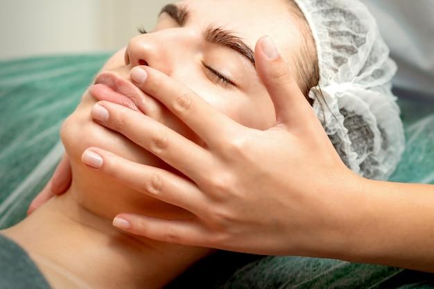 De jonge vrouw die gezichtsmassage ontvangen door dient in kuuroord medische salon